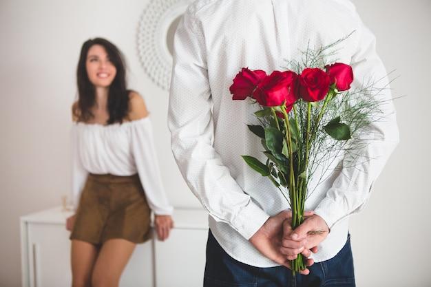 Девушка держит воздушные шары с формы сердца в то время как ее парень держит букет из роз в спине