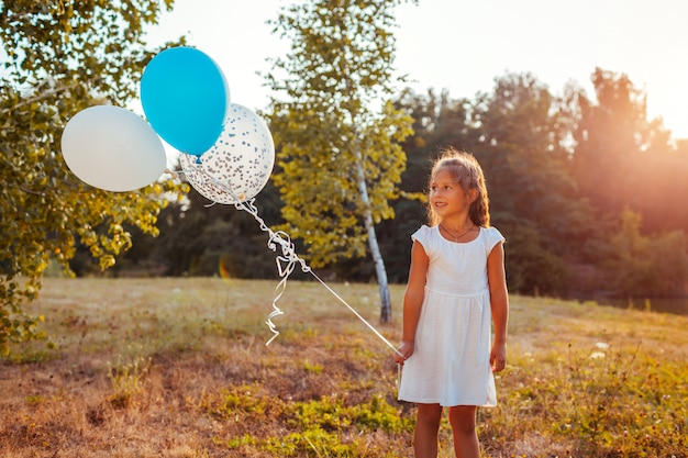 Girl holding baloons outdoors. kid having fun in summer park. happy child looking at