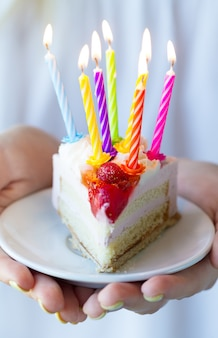 Girl holding beautiful appetizing birthday cake with many candles. closeup.