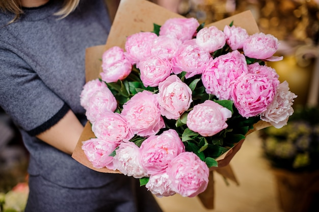 Girl holding a beautiful bouquet of rose colour peonies