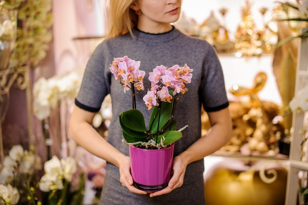 Girl holding a beautiful rose colour orchid in pink pot