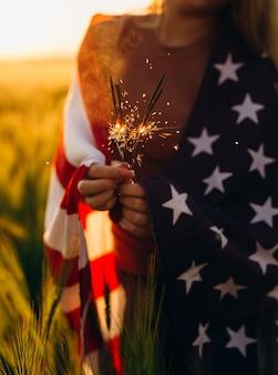 Девушка держит бенгальский огонь с американским флагом на закате