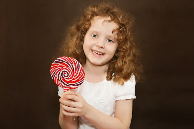 Girl holding a big  lollipop, toned photo on brown background.