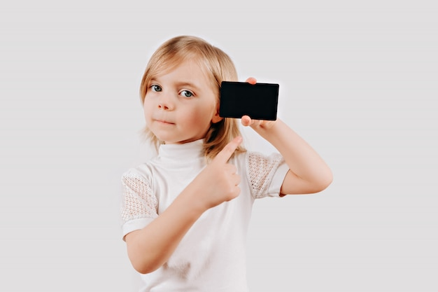 Girl holding black card in hand. kid showing credit card. mock up