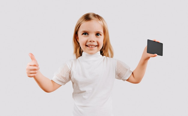 Girl holding black card in hand. kid with credit card. mock up