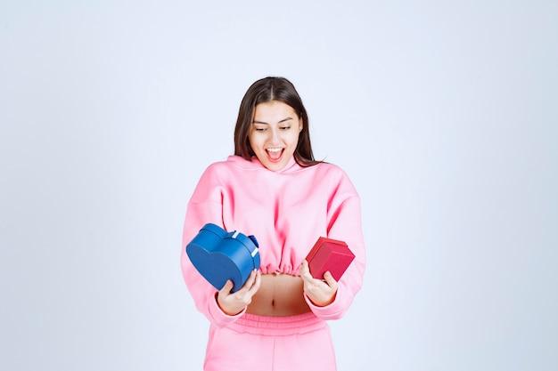 Девушка держит синие и красные подарочные коробки в обеих руках.