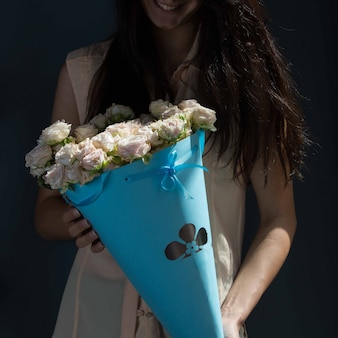 A girl holding a blue cardboard bouquet of white roses in hands on a green wall