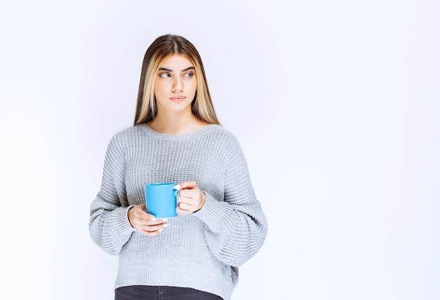 Ragazza che tiene una tazza da caffè blu e la promuove.