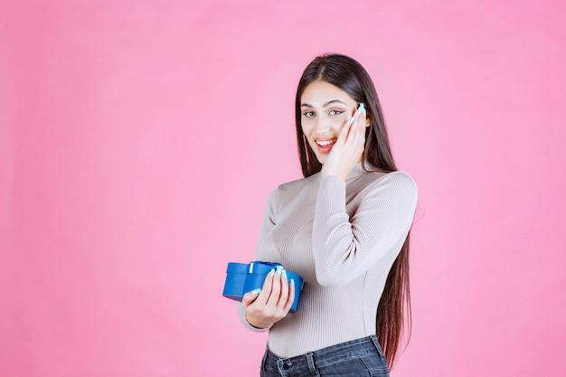 Ragazza che tiene una confezione regalo blu e sorridente
