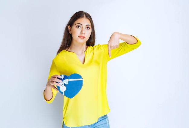 Ragazza che tiene una confezione regalo blu a forma di cuore e chiama qualcuno per presentarla.