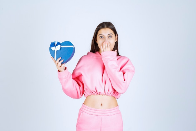 Ragazza che tiene una confezione regalo a forma di cuore blu e lo dimostra