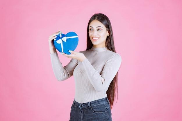 Ragazza che tiene un giftbox a forma di cuore blu e lo dimostra
