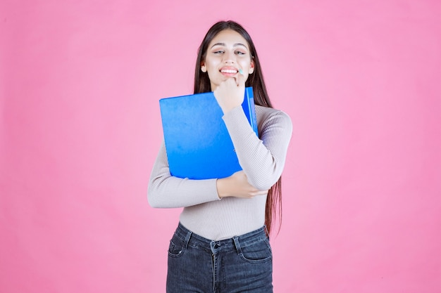 Girl holding a blue project folder and looks successful and happy