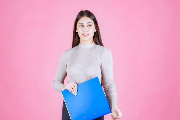 Girl holding a blue report folder and looks tired