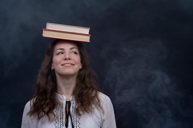 Девушка держит книги на голове концепция гениальной медитации и знаний
