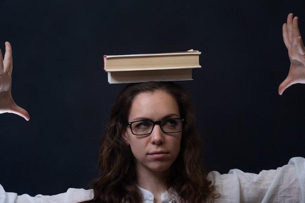 Девушка держит книги на голове концепция мудрости, знания и образования