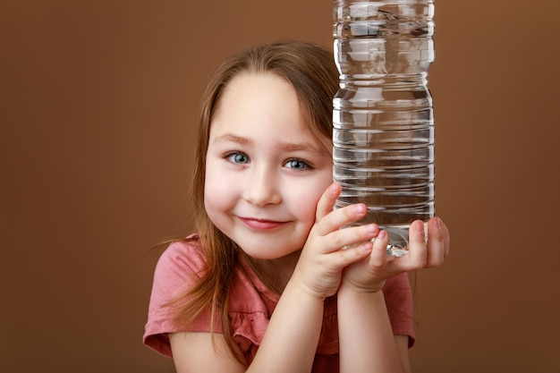 Girl holding bottle of water in hands