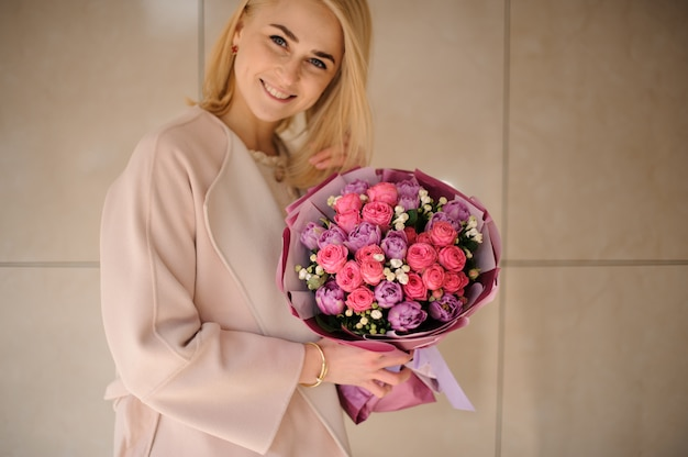 Girl holding bouquet of peonies and roses