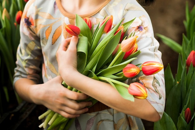 Girl holding a bouquet of tulips grown in a greenhouse