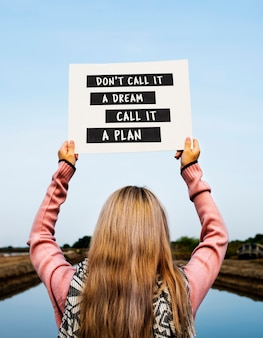 Girl holding don't call it a dream call it a plan placard