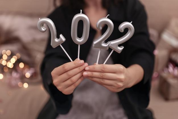 Ragazza con candele sotto forma di numeri 2022, concetto di celebrazione del nuovo anno.