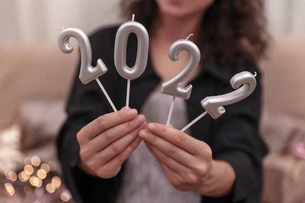 数字2022、新年のお祝いの概念の形でキャンドルを保持している女の子。