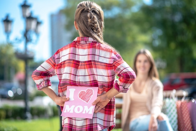 Девочка держит карту для своей мамы, сидя на скамейке в парке