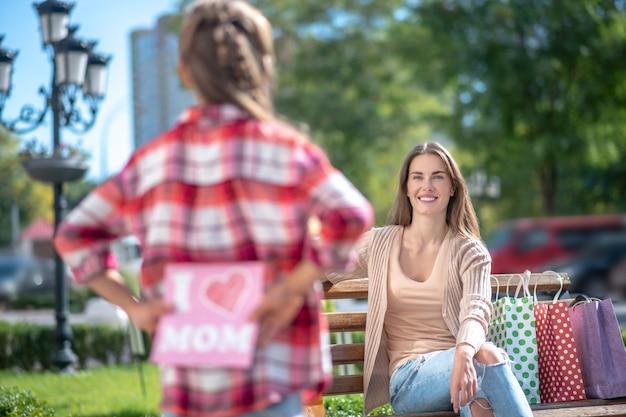 Девушка держит карту для своей улыбающейся мамы, сидящей на скамейке в парке