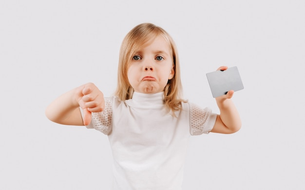 Girl holding card in hand and shows dislike. kid showing credit card. mock up