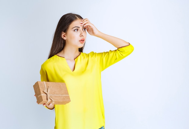 Girl holding a cardboard gift box and looks confised or thoughtful.