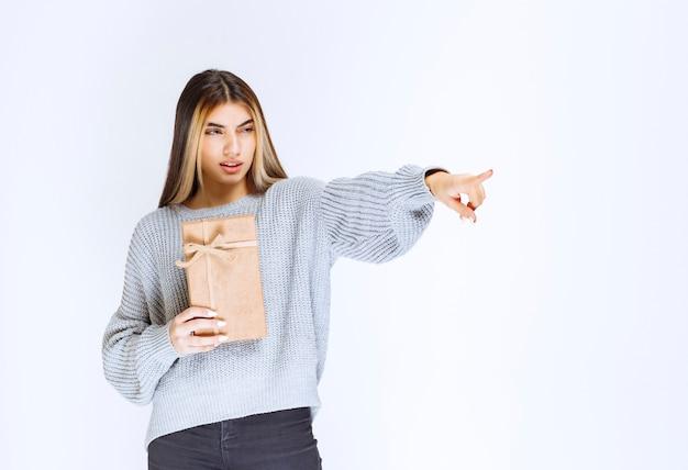 Ragazza che tiene una scatola regalo di cartone e indica un ricevitore da parte.
