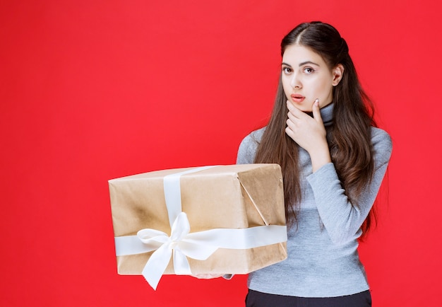 Girl holding a cardboard gift box and thinking.