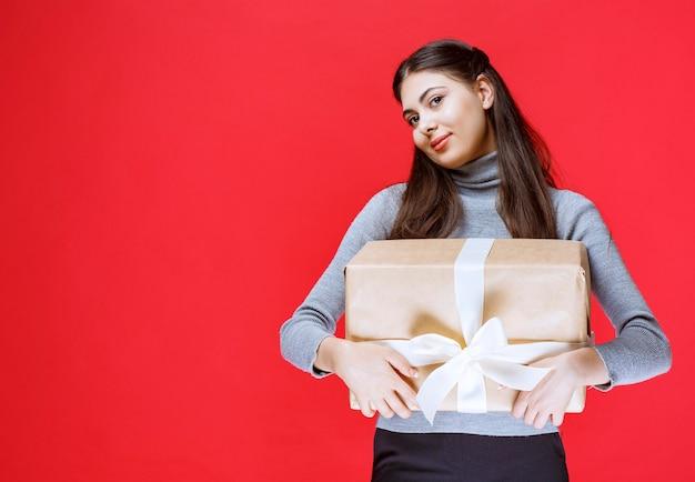 Ragazza in possesso di una confezione regalo di cartone avvolta con nastro di tulle bianco.