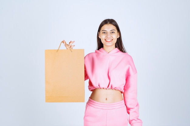 Girl holding a cardboard shopping bag and feeling excited.