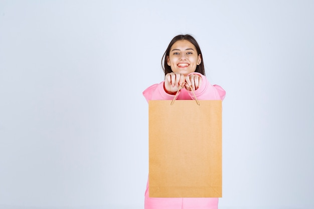 Girl holding a cardboard shopping bag and offering it to the customer.
