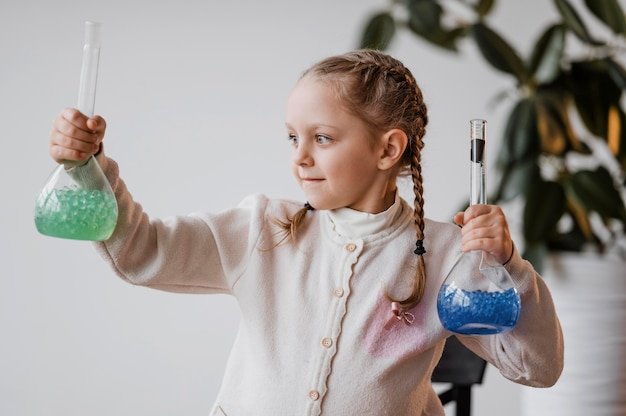 Girl holding chemical elements in recipients