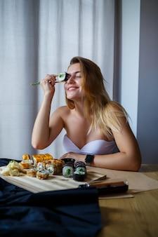 箸巻き寿司を持っている女の子。おいしい新鮮な日本の寿司を食べる若い女性。