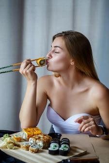箸巻き寿司を持っている女の子。美味しいお寿司を食べる若い女性。