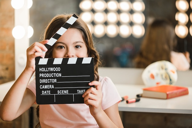 Girl holding clapperboard in front of her mouth