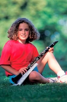Девушка держит кларнет в парке