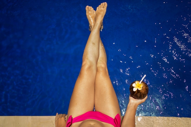 Girl holding coconut drink in the blue pool, slim legs, instagram style. tropical fruit diet. summer holiday idyllic.