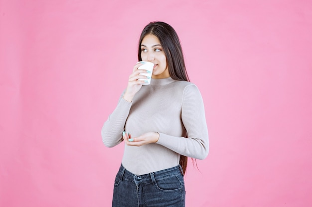 Girl holding a coffee cup and drinking it