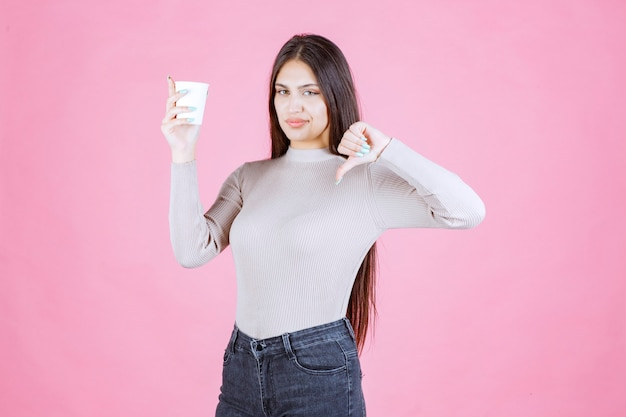 Girl holding a coffee cup and showing thumb down sign