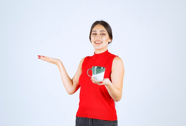 Girl holding a coffee mug and pointing to the left.