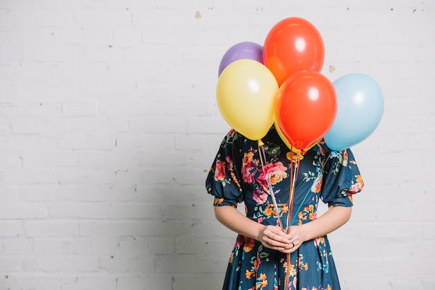 Girl holding colorful balloons in front of her face standing against wall