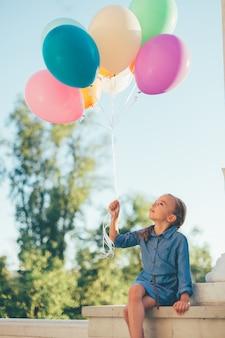 Девочка держит разноцветных шаров, глядя на них