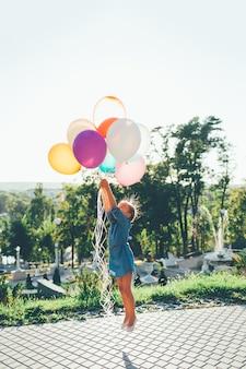 Девочка держит разноцветных шаров, простирающихся до неба
