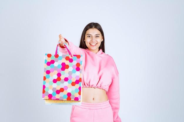 カラフルな買い物袋を持って興奮している女の子。