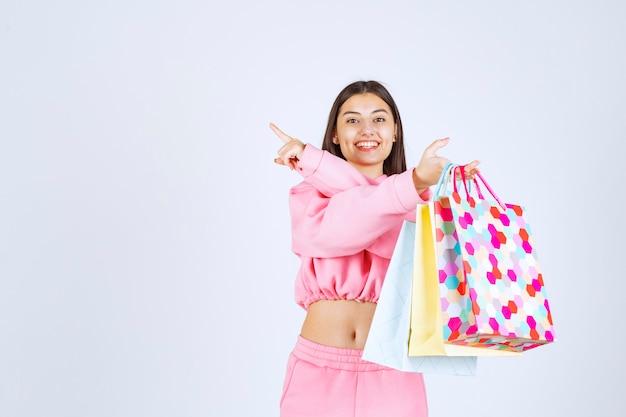 カラフルな買い物袋を持って、どこか上を指している女の子。