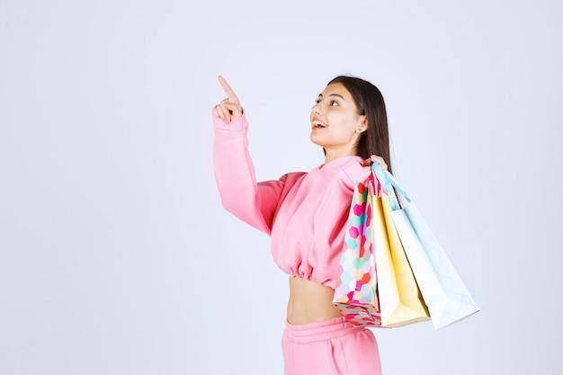 Girl holding colorful shopping bags back at her shoulder.